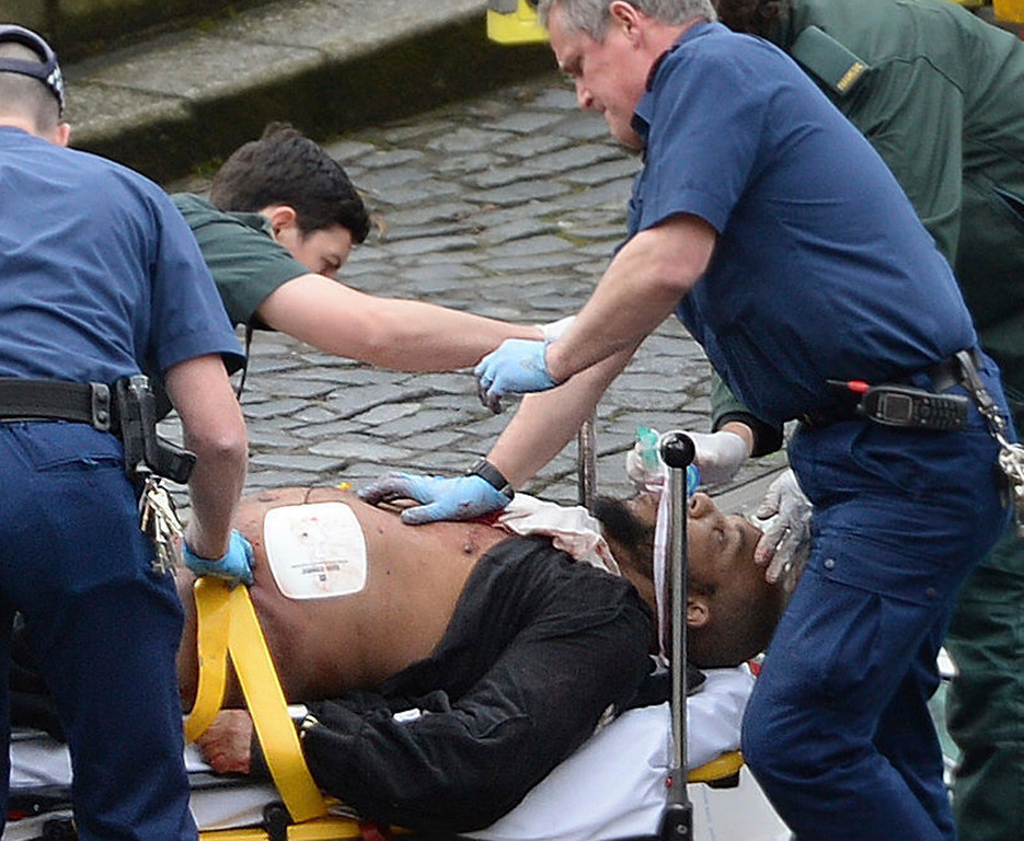 ". An attacker is treated by emergency services outside the Houses of Parliament London, Wednesday, March 22, 2017.  London police say they are treating a gun and knife incident at Britain\'s Parliament ""as a terrorist incident until we know otherwise.\"" The Metropolitan Police says in a statement that the incident is ongoing. It is urging people to stay away from the area. Officials say a man with a knife attacked a police officer at Parliament and was shot by officers. Nearby, witnesses say a vehicle struck several people on the Westminster Bridge.  (Stefan Rousseau/PA via AP)."