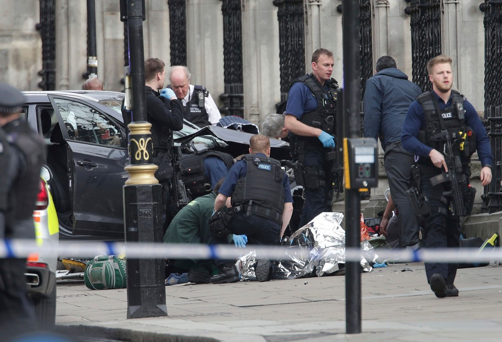". Emergency personnel tend to an injured person close to the Palace of Westminster, London, Wednesday, March 22, 2017.  London police say officers called to a \'firearms incident\' on Westminster Bridge, near Parliament. The leader of Britain\'s House of Commons says a man has been shot by police at Parliament. David Liddington also said there were ""reports of further violent incidents in the vicinity.\""  Britain\'s MI5 says it is too early to say if the incident is terror-related. (Yui Mok/PA via AP)."