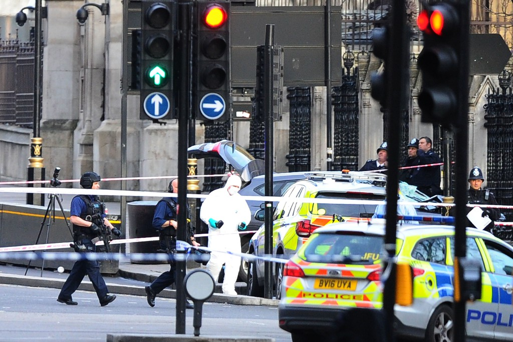". Armed police officers carry their weapons as work near a grey vehicle that crashed into the railings of the Houses of Parliament in central London on March 22, 2017, during an emergency incident. British police shot a suspected attacker outside the Houses of Parliament in London on Wednesday after an officer was stabbed in what police said was a ""terrorist\"" incident. One woman has died and others have \""catastrophic\"" injuries following a suspected terror attack outside the British parliament, local media reported on Wednesday citing a junior doctor. (DANIEL LEAL-OLIVAS/AFP/Getty Images)"