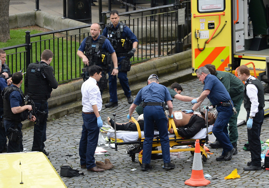 ". A man is treated by emergency services  as police look on at the scene outside the Houses of Parliament London, Wednesday, March 22, 2017.  London police say they are treating a gun and knife incident at Britain\'s Parliament ""as a terrorist incident until we know otherwise.\"" The Metropolitan Police says in a statement that the incident is ongoing. It is urging people to stay away from the area. Officials say a man with a knife attacked a police officer at Parliament and was shot by officers. Nearby, witnesses say a vehicle struck several people on the Westminster Bridge.  (Stefan Rousseau/PA via AP)."