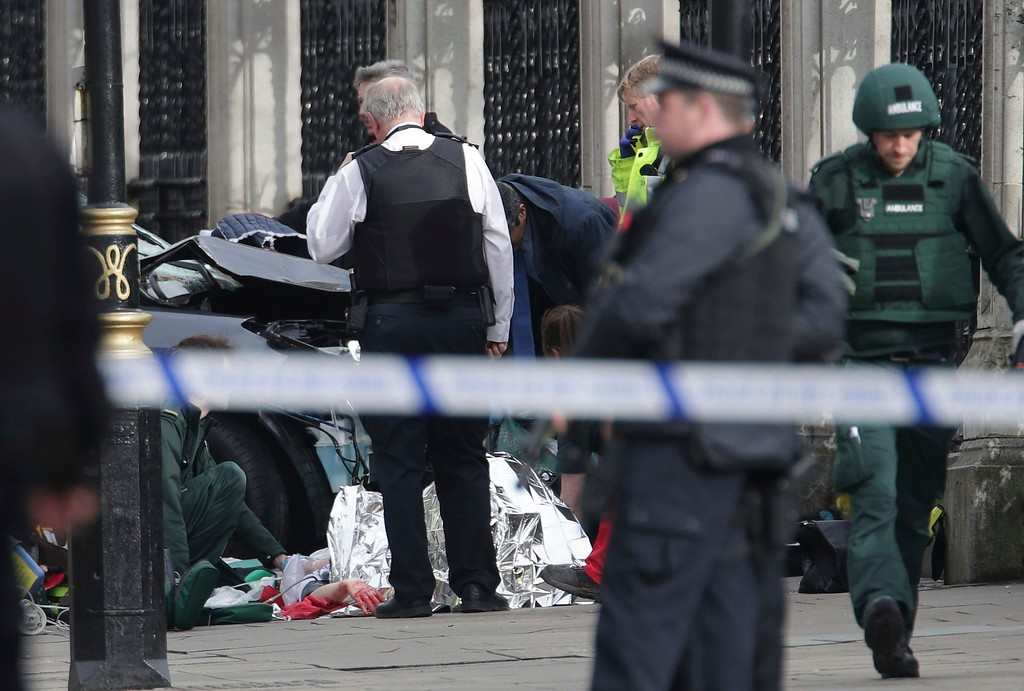 ". Emergency personnel tend to an injured person close to the Palace of Westminster, London, Wednesday, March 22, 2017.  London police say officers called to a \'firearms incident\' on Westminster Bridge, near Parliament. The leader of Britain\'s House of Commons says a man has been shot by police at Parliament. David Liddington also said there were ""reports of further violent incidents in the vicinity.\""  London\'s police said officers had been called to a firearms incident on Westminster Bridge, near the parliament. Britain\'s MI5 says it is too early to say if the incident is terror-related. (Yui Mok/PA via AP)."