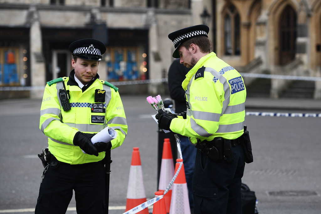. LONDON, ENGLAND - MARCH 23:  A Police officer holds flowers near Parliament Square on March 23, 2017 in London, England.  Four people have been killed and around 40 people injured following yesterday\'s attack by the Houses of Parliament in Westminster.  (Photo by Carl Court/Getty Images)