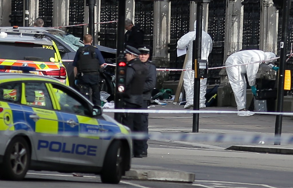 ". Armed police officers carry their weapons as forensics officers work near a grey vehicle that crashed into the railings of the Houses of Parliament in central London on March 22, 2017, during an emergency incident. British police shot a suspected attacker outside the Houses of Parliament in London on Wednesday after an officer was stabbed in what police said was a ""terrorist\"" incident. One woman has died and others have \""catastrophic\"" injuries following a suspected terror attack outside the British parliament, local media reported on Wednesday citing a junior doctor. (DANIEL LEAL-OLIVAS/AFP/Getty Images)"