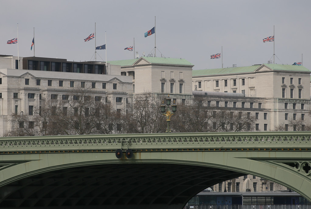 . Flags fly at half staff above the Ministry of Defence and other government buildings in London Thursday March 23, 2017, with Westminster Bridge the scene of an attack in foreground.  On Wednesday a knife-wielding man went on a deadly rampage, first driving a car into pedestrians on Westminster Bridge then stabbing a police officer to death before being fatally shot by police within Parliament\'s grounds in London.  (AP Photo/Tim Ireland)