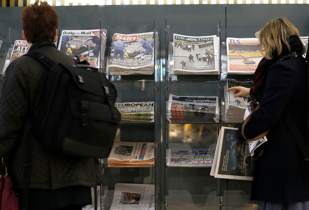 . People look at a newspaper stand showing papers with coverage of Wednesday\'s attack in London, Thursday March 23, 2017. On Wednesday a knife-wielding man went on a deadly rampage, first  driving a car into pedestrians before stabbing a police officer to death and then was fatally shot by police within Parliament\'s grounds in London.  Five people were killed, including the assailant.(AP Photo/Kirsty Wigglesworth)