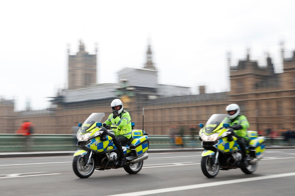 . Police on motorcycles ride across Westminster Bridge away from the Houses of Parliament in central London on March 23, 2017 after the bridge reopened to traffic  following its closure during the March 22 terror attack.  Britain\'s parliament reopened on Thursday with a minute\'s silence in a gesture of defiance a day after an attacker sowed terror in the heart of Westminster, killing three people before being shot dead. Sombre-looking lawmakers in a packed House of Commons chamber bowed their heads and police officers also marked the silence standing outside the headquarters of London\'s Metropolitan Police nearby. (ADRIAN DENNIS/AFP/Getty Images)