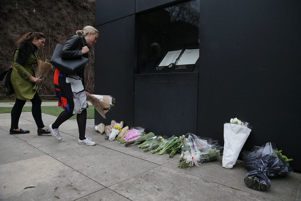 . People add bunches of flowers to the floral tributes in honour of police officer Keith Palmer, who was killed during the March 22 terror attack in Westminster, at the National Police Memorial in Westminster, central London on March 23, 2017.  Britain\'s parliament reopened on Thursday with a minute\'s silence in a gesture of defiance a day after an attacker sowed terror in the heart of Westminster, killing three people before being shot dead. Sombre-looking lawmakers in a packed House of Commons chamber bowed their heads and police officers also marked the silence standing outside the headquarters of London\'s Metropolitan Police nearby. (DANIEL LEAL-OLIVAS/AFP/Getty Images)