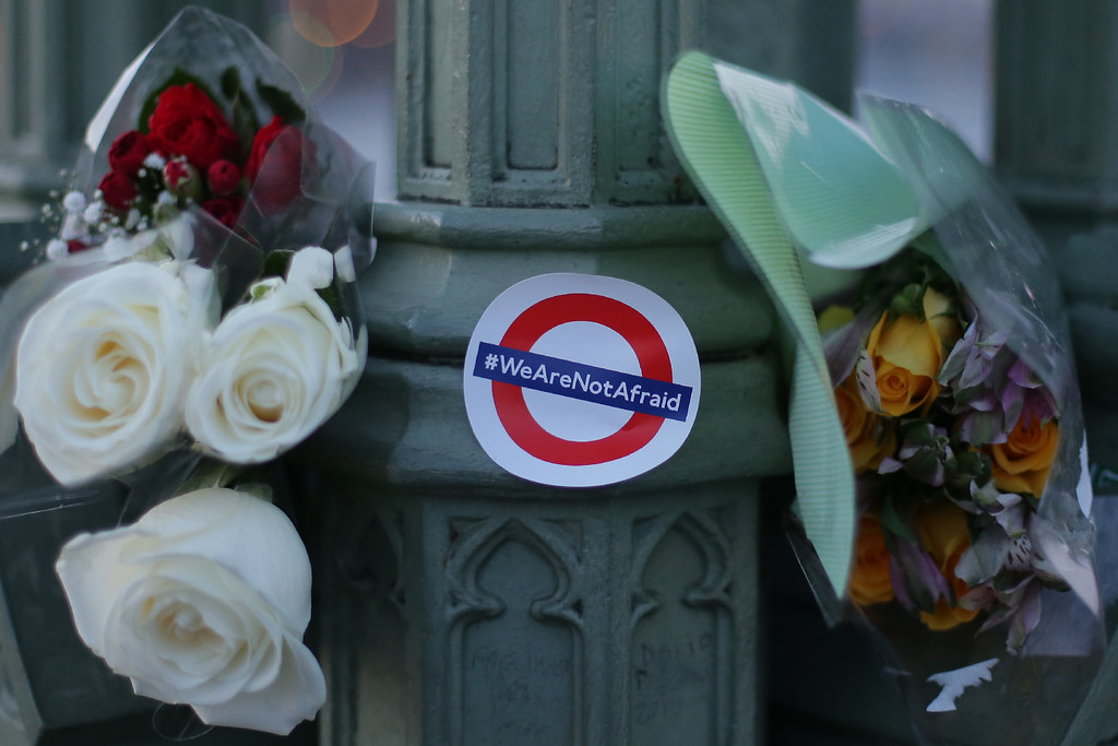 ". Bunches of flowers and a sticker showing the London Underground logo and the words ""We are not afraid\"" in honour of the victims of the March 22 terror attack are pictured in central London on March 23, 2017.  Britain\'s parliament reopened on Thursday with a minute\'s silence in a gesture of defiance a day after an attacker sowed terror in the heart of Westminster, killing three people before being shot dead. Sombre-looking lawmakers in a packed House of Commons chamber bowed their heads and police officers also marked the silence standing outside the headquarters of London\'s Metropolitan Police nearby. (DANIEL LEAL-OLIVAS/AFP/Getty Images)"