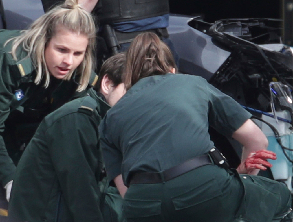 ". A bloodied hand is  emerges as a person is treated at the scene outside the Houses of Parliament London, Wednesday, March 22, 2017.  London police say they are treating a gun and knife incident at Britain\'s Parliament ""as a terrorist incident until we know otherwise.\"" The Metropolitan Police says in a statement that the incident is ongoing. It is urging people to stay away from the area. Officials say a man with a knife attacked a police officer at Parliament and was shot by officers. Nearby, witnesses say a vehicle struck several people on the Westminster Bridge.  (Yui Mok/PA via AP)."