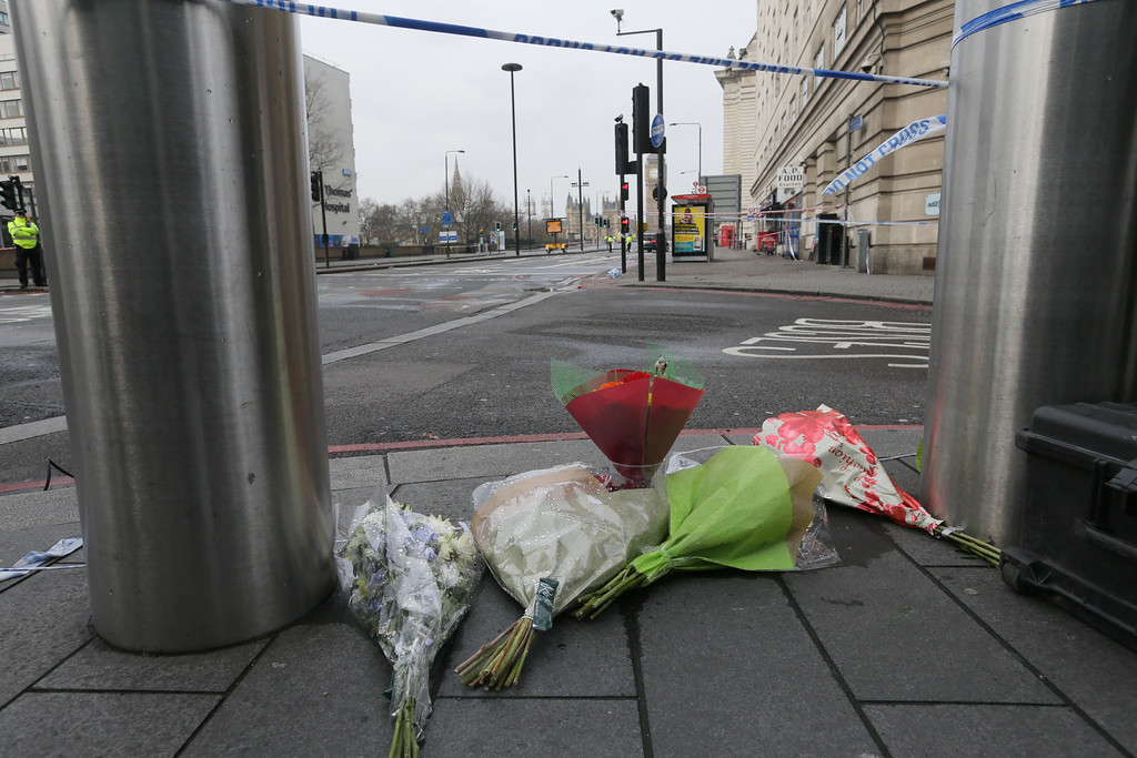 . Flower tributes are left on the pavement on the edge of a police cordon near to parliament, centre background, with St.Thomas\' Hospital, left, where some of the injured were taken for treatment, in London, Thursday March 23, 2017.  On Wednesday a man went on a deadly rampage, first driving a car into pedestrians then stabbing a police officer to death before being fatally shot by police within Parliament\'s grounds in London. (AP Photo/Tim Ireland)