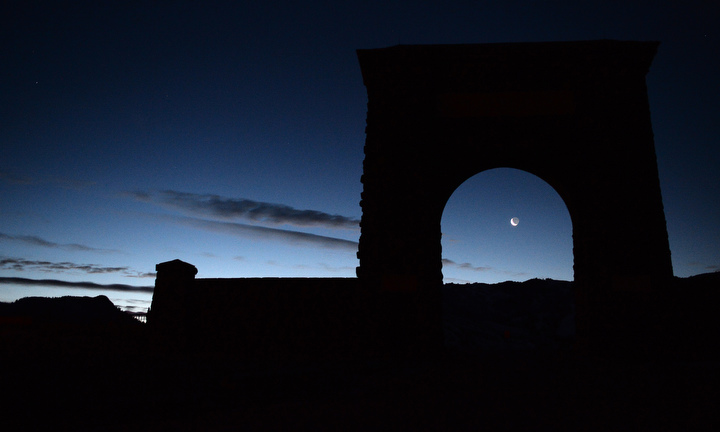 . The new moon rises under Roosevelt Arch at the northwest entrance to Yellowstone. PHOTO:Will Lester