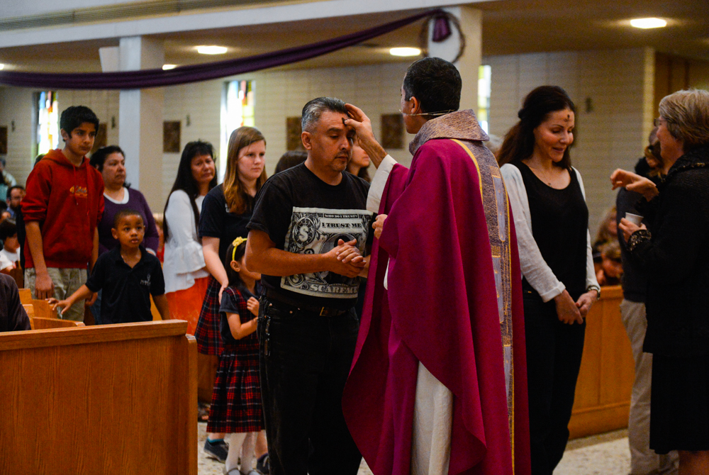 Description of . Parishioners receive ashes on their forehead during Ash Wednesday at the Holy Name of Jesus Catholic Community, Inc. in Redlands, CA on Wednesday, March 5, 2014. Ash Wednesday marks the beginning of Lenten season, a holy time when Catholics prepare for Easter. (Photo by Rachel Luna / Redlands Daily Facts)