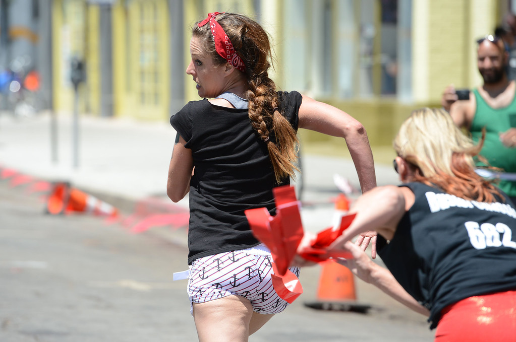 . Ashley Hull is chased during the first Running of the Dames, along Pine Avenue between and 8th Streets. Fashioned after the Running of the Bulls, local derby girls chase down runners along a course, grabbing two red flags off the waist of the runner. Last runner standing wins the race.  Long Beach Calif., Saturday May 31,  2014.     (Photo by Stephen Carr / Daily Breeze)