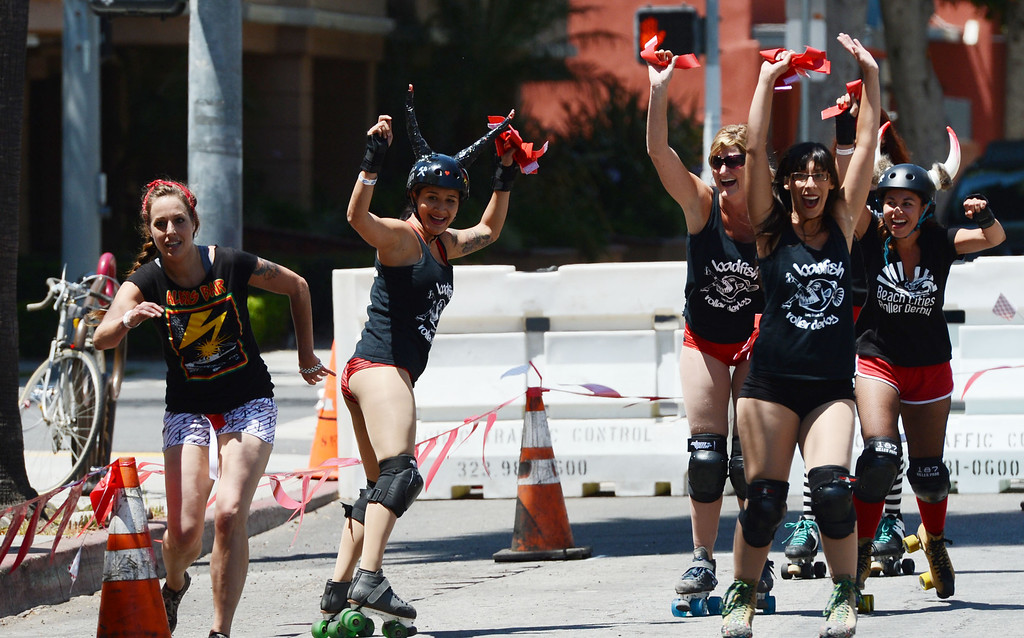 . Ashley Hull is chased down during the first Running of the Dames, along Pine Avenue between and 8th Streets. Fashioned after the Running of the Bulls, local derby girls chase down runners along a course, grabbing two red flags off the waist of the runner. Last runner standing wins the race.  Long Beach Calif., Saturday May 31,  2014.     (Photo by Stephen Carr / Daily Breeze)