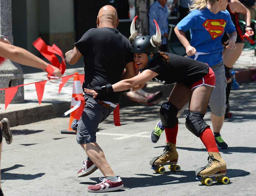 """. Press -Telegram reporter Richard Guzman,left, is rundown by  Beach Cities Roller Derby\'s Ashley  \"""" Bambi \""""  Smith in the first Running of the Dames along Pine Avenue between and 8th Streets. Fashioned after the Running of the Bulls, local derby girls chase down runners along a course, grabbing two red flags off the waist of the runner. Last runner standing wins the race.  Long Beach Calif., Saturday May 31,  2014.     (Photo by Stephen Carr / Daily Breeze)"""