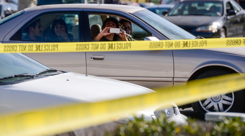 Description of . People gather and watch police investigate the scene of a homicide that took place inside Domino's Pizza on the 1600 block of E. Highland Avenue in San Bernardino, CA on Wednesday, Feb. 12, 2014. The female victim, who was a worker at Domino's Pizza, was pronounced dead at the hospital, according to authorities. (Photo by Rachel Luna / San Bernardino Sun)