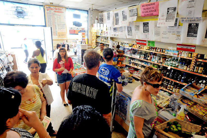 ". Customers buy Powerball tickets at Alcon Liquor in Canoga Park, CA Friday.  The liquor store is listed as a ""Lucky Retailer\"" on the California Lottery website.  By Friday at noon the Powerball jackpot had grown to an estimated 00 million, the largest amount in the game\'s history.(Andy Holzman/Staff Photographer)"