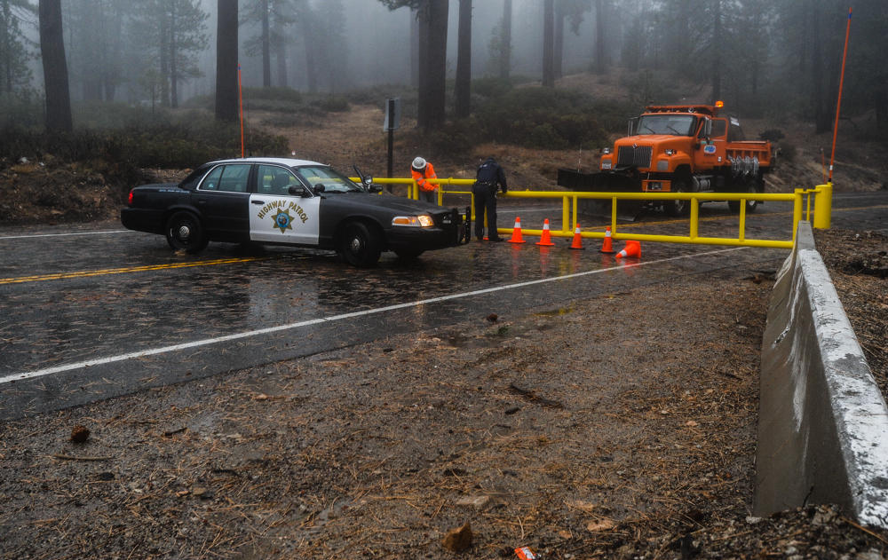 . Caltrans and a CHP officer close-off Highway 18 to traffic in Running Springs, CA on Friday, Feb. 28, 2014. Rock and mudslides from heavy rainfall caused the road closure between Running Springs and Big Bear Lake. (Photo by Rachel Luna / San Bernardino Sun)