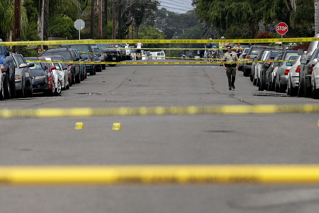 . A Santa Barbara County deputy sheriff walks along the street near the scene of a shooting on Saturday, May 24, 2014, in Isla Vista, Calif. A drive-by shooter went on a rampage near a Santa Barbara university campus that left seven people dead, including the attacker, and others wounded, authorities said Saturday. (AP Photo/Jae C. Hong)
