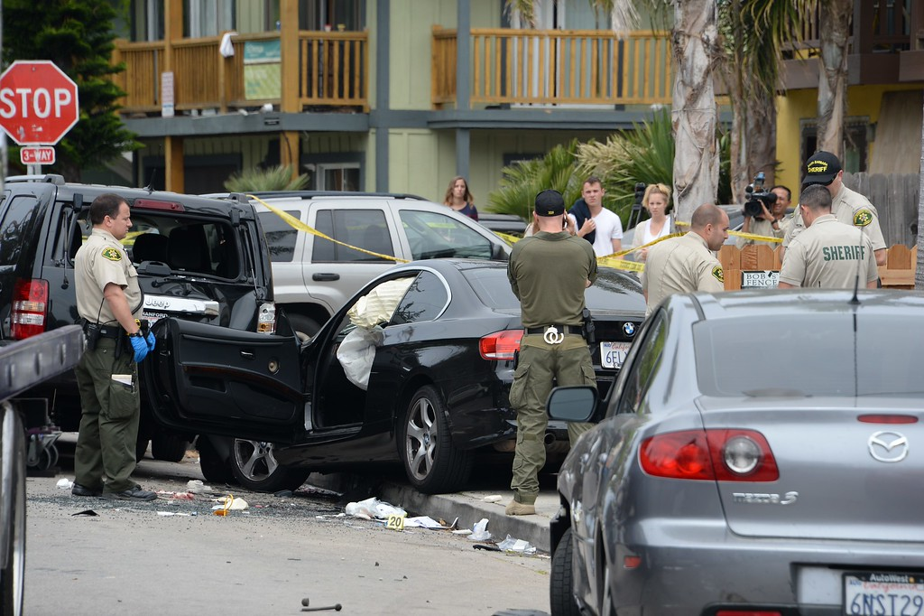 """. Investigators inspect a suspected gunman\'s car on May 24, 2014, after a drive-by shooting in Isla Vista, California, a beach community next to the University of California Santa Barbara. Seven people, including the gunman, were killed and seven others wounded in the May 23 mass shooting, Santa Barbara County Sheriff Bill Brown said Saturday. Brown said at a pre-dawn press conference that the shooting in the town of Isla Vista \""""appears to be a mass murder situation.\"""" Driving a black BMW, the suspect opened fire on pedestrians from his vehicle at several locations in the town.            (ROBYN BECK/AFP/Getty Images)"""