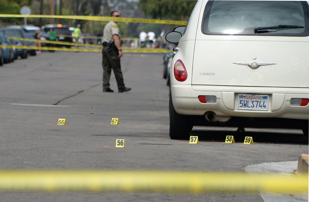 """. Investigators mark evidence on May 24, 2014, after a drive-by shooting in Isla Vista, California, a beach community next to the University of California Santa Barbara. Seven people, including the gunman, were killed and seven others wounded in the May 23 mass shooting, Santa Barbara County Sheriff Bill Brown said Saturday. Brown said at a pre-dawn press conference that the shooting in the town of Isla Vista \""""appears to be a mass murder situation.\"""" Driving a black BMW, the suspect opened fire on pedestrians from his vehicle at several locations in the town.            (ROBYN BECK/AFP/Getty Images)"""