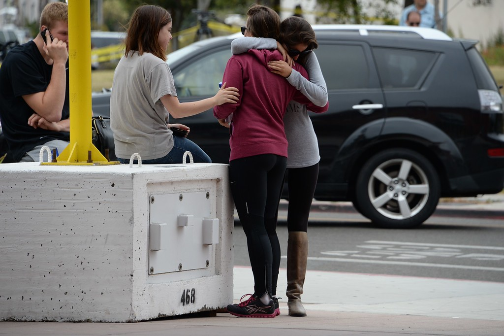 """. Students hug on May 24, 2014, after a drive-by shooting in Isla Vista, California, a beach community next to the University of California Santa Barbara. Seven people, including the gunman, were killed and seven others wounded in the May 23 mass shooting, Santa Barbara County Sheriff Bill Brown said Saturday. Brown said at a pre-dawn press conference that the shooting in the town of Isla Vista \""""appears to be a mass murder situation.\"""" Driving a black BMW, the suspect opened fire on pedestrians from his vehicle at several locations in the town.            (ROBYN BECK/AFP/Getty Images)"""