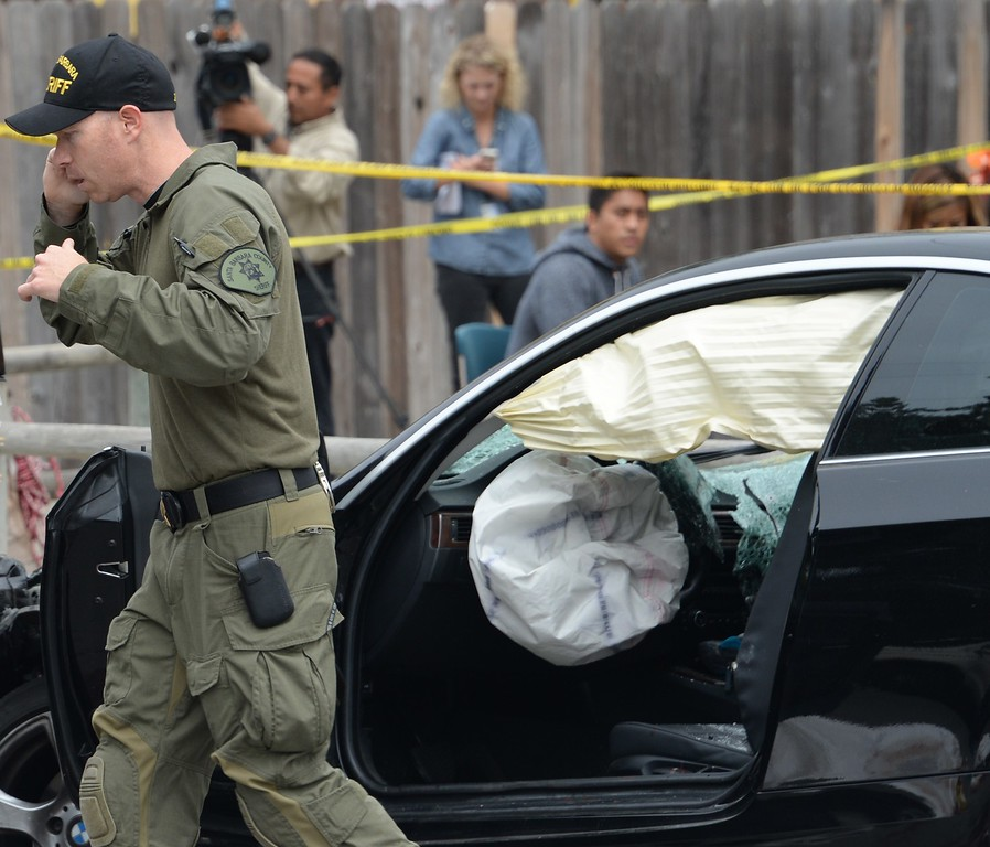 """. An investigator speaks on a cell phone while inspecting a suspected gunman\'s car on May 24, 2014, after a drive-by shooting in Isla Vista, California, a beach community next to the University of California Santa Barbara. Seven people, including the gunman, were killed and seven others wounded in the May 23 mass shooting, Santa Barbara County Sheriff Bill Brown said Saturday. Brown said at a pre-dawn press conference that the shooting in the town of Isla Vista \""""appears to be a mass murder situation.\"""" Driving a black BMW, the suspect opened fire on pedestrians from his vehicle at several locations in the town.            (ROBYN BECK/AFP/Getty Images)"""