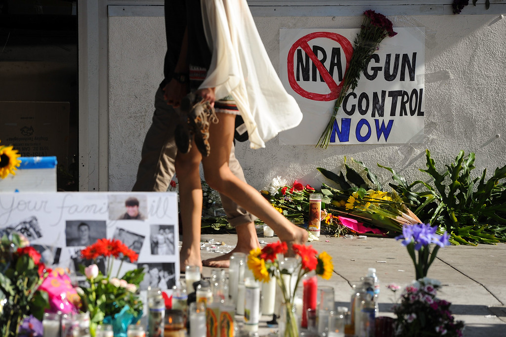 . People walk by a memorial and a gun control sign in front of the IV Deli Mart, Sunday, May 25, 2014, where Christopher Michaels-Martinez was killed during Friday night\'s shootings in Isla Vista. (Photo by Michael Owen Baker/Los Angeles Daily News)