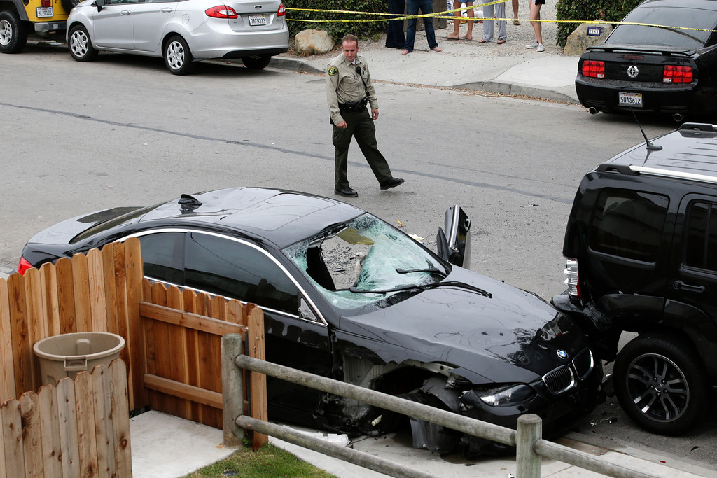 . A Santa Barbara County deputy sheriff looks at the black BMW sedan driven by a drive-by shooter on Saturday, May 24, 2014, in Isla Vista, Calif. The shooter went on a rampage near a Santa Barbara university campus that left seven people dead, including the attacker, and others wounded, authorities said Saturday. (AP Photo/Jae C. Hong)