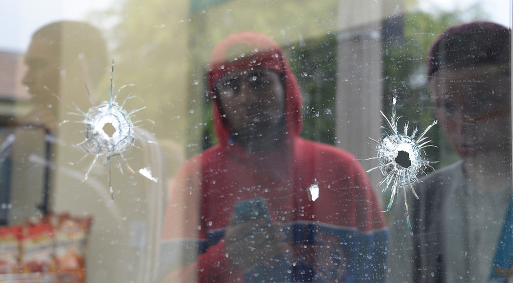 . May 24-,2014. Isla Vista, CA. UCSB students gather at IV Deli Mart where bullet holes are seen in the glass windows where one person was killed by the drive-by shooter Friday night. Seven people are dead, including the attacker, and seven others wounded, authorities said Saturday.  The gunman got into two gun battles with deputies Friday night in the beachside community of Isla Vista before crashing his black BMW into a parked car. Photo by Gene Blevins/LA Daily News