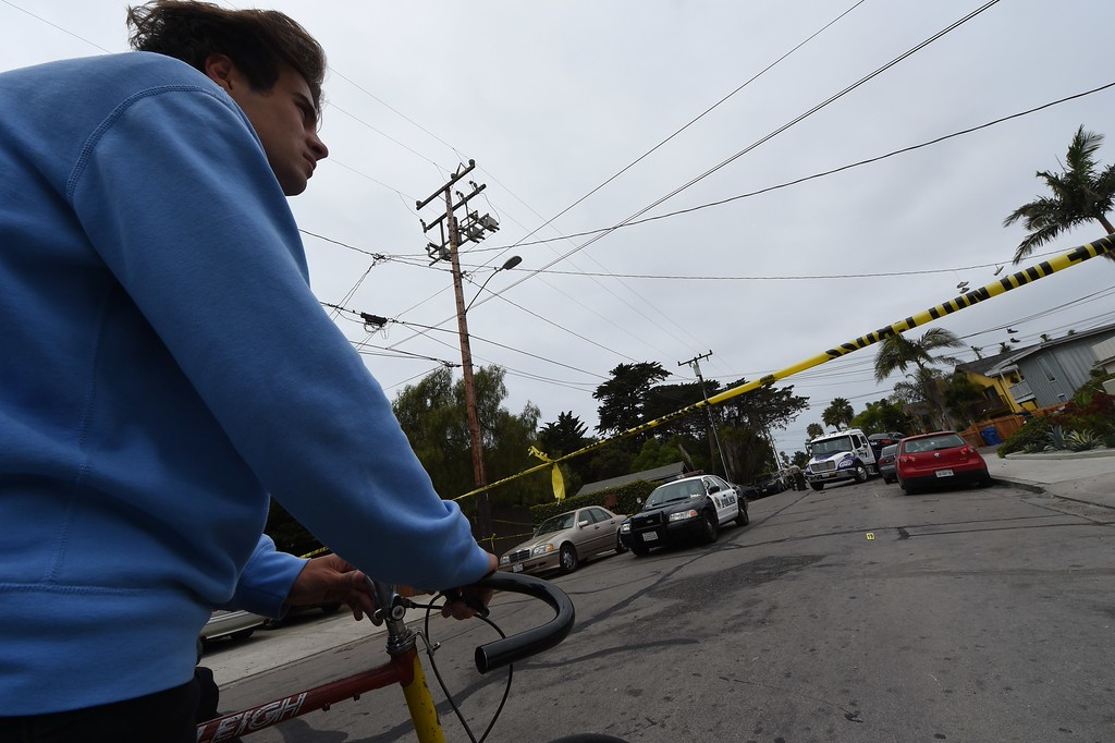 """. University of California Santa Barbara (UCSB) student Thor Blough, 22, watches from behind police lines as the car driven by a suspected gunman is moved in Isla Vista, California, on May 24, 2014.  A friend of Blough\'s, also a student, was shot in the leg but survived and is in hospital. Seven people, including the gunman, were killed and seven others wounded in the May 23 mass shooting, Santa Barbara County Sheriff Bill Brown said Saturday. Brown said at a pre-dawn press conference that the shooting in the town of Isla Vista \""""appears to be a mass murder situation.\"""" Driving a black BMW, the suspect opened fire on  pedestrians from his vehicle at several locations in the town.            (ROBYN BECK/AFP/Getty Images)"""