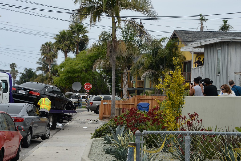 """. Residents watch on May 24, 2014, as a suspected gunman\'s car is removed after a drive-by shooting in Isla Vista, California, a beach community next to the University of California Santa Barbara. Seven people, including the gunman, were killed and seven others wounded in the May 23 mass shooting, Santa Barbara County Sheriff Bill Brown said Saturday. Brown said at a pre-dawn press conference that the shooting in the town of Isla Vista \""""appears to be a mass murder situation.\"""" Driving a black BMW, the suspect opened fire on pedestrians from his vehicle at several locations in the town.            (ROBYN BECK/AFP/Getty Images)"""