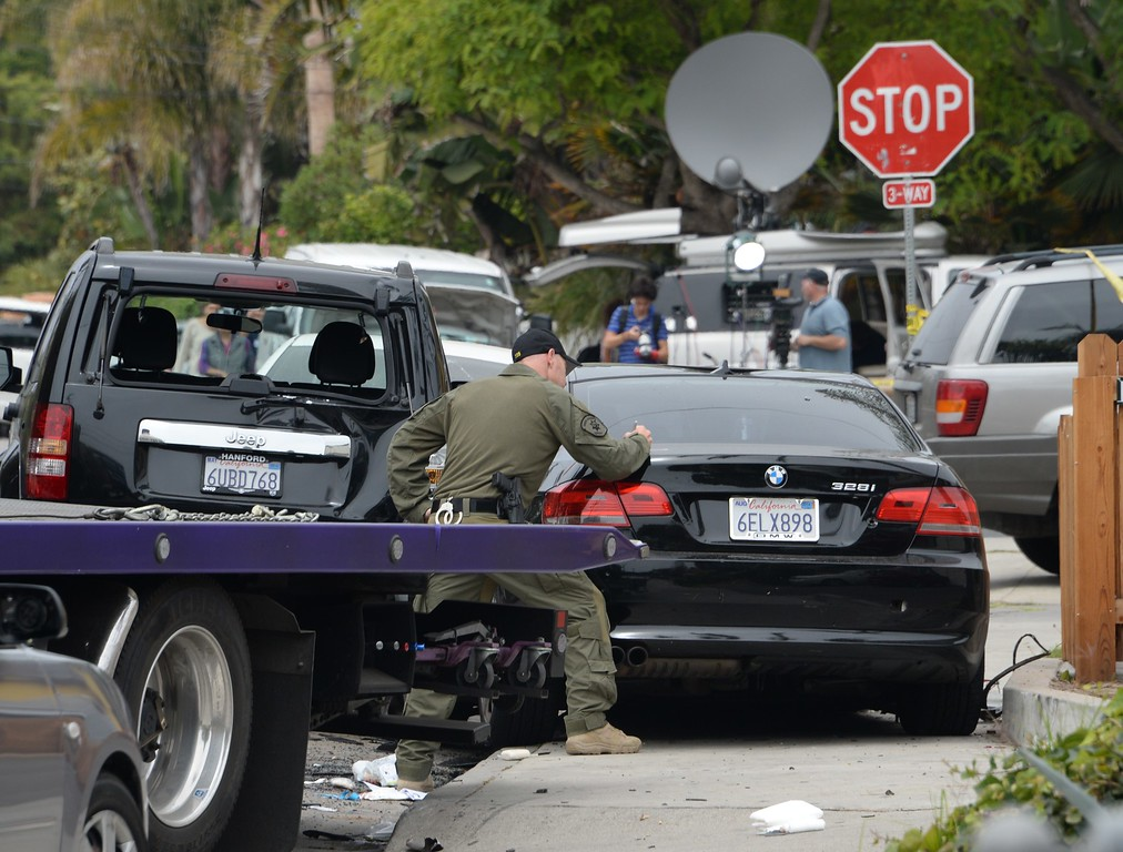 """. An investigator inspects a suspected gunman\'s car on May 24, 2014, after a drive-by shooting in Isla Vista, California, a beach community next to the University of California Santa Barbara. Seven people, including the gunman, were killed and seven others wounded in the May 23 mass shooting, Santa Barbara County Sheriff Bill Brown said Saturday. Brown said at a pre-dawn press conference that the shooting in the town of Isla Vista \""""appears to be a mass murder situation.\"""" Driving a black BMW, the suspect opened fire on pedestrians from his vehicle at several locations in the town.           (ROBYN BECK/AFP/Getty Images)"""