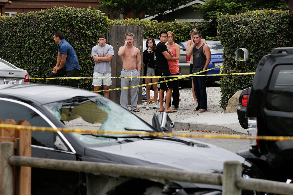 . People look at a black BMW sedan driven by a drive-by shooter on Saturday, May 24, 2014, in Isla Vista, Calif. The shooter went on a rampage near a Santa Barbara university campus that left seven people dead, including the attacker, and seven others wounded, authorities said Saturday. (AP Photo/Jae C. Hong)