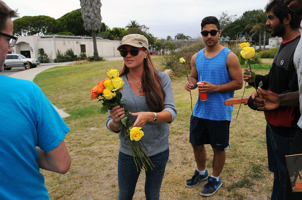 """. Santa Barbara resident Caitlyn Dixon hands out flowers as a \""""random act of kindness\"""" in Isla Vista, Saturday, May 24, 2014. (Photo by Michael Owen Baker/Los Angeles Daily News)"""