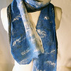 "Sea.  Group B.<br /> <br /> Blue merino/silk blend edged with natural ivory merino, hand felted to hand dyed black silk habutai, embellished with tencel (wood-sourced) fibers. On the side with exposed silk, the blue fiber has migrated through to provide a soft heather over the black-- and that satisfying nuno scrunch we love. <br /> <br /> Light and elegant. Cuts chill with moderate warmth (though not for Minnesota in February, except maybe inside). <br /> <br /> Hand wash lukewarm/gentle, roll in towel, dry flat or hang to dry, touchup iron the edges if you want. <br /> <br /> 9x66"" -- plenty to make an extra wrap around your dainty neck.<br /> <br /> Monitors vary. I checked color on two; they looked pretty different. Tried to average for general accuracy. But your results may differ. This is a pure, fairly intense blue, sometimes called ""Chagall."""