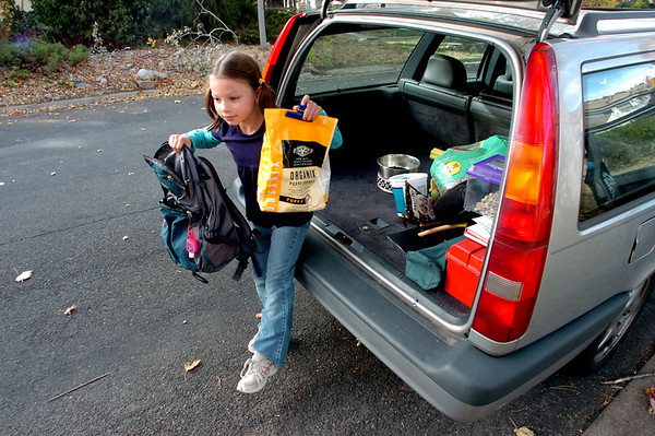 COBOU103.JPG Evie Worthington, 7, helps her family unpack their car after the family returned to their Boulder home on Saturday morning October 30, 2010. The family of 4 evacuated from the Dome Fire and stayed overnight in a local hotel.<br /> Photo by Paul Aiken / The Camera