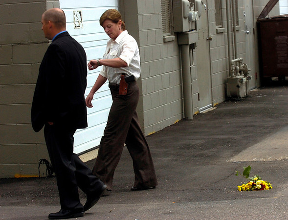 WALK.JPG On Wednesday Boulder police investigators walk past a bouquet of flowers left at the rear  of the Boulder Stove & Flooring store during their final walk-through of the scene of the fatal shooting on Monday.<br /> Photo by Paul Aiken / The Boulder Camera