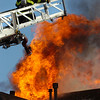 FIRE58.JPG A firefighter rises above the flames shooting from the roof as they work against a fire in Superior on <br /> Thursday afternoon. <br /> Photo by Paul Aiken /  August 26, 2010.