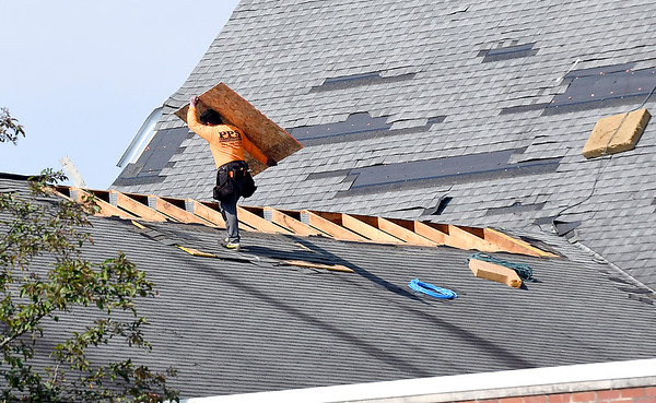 John P. Cleary   The Herald Bulletin <br /> Tornado cleanup starts in the Pendleton area after Monday's storms. Repairs begin on the roof of Pendleton First United Methodist Church.