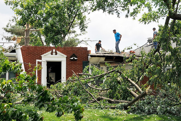 John P. Cleary   The Herald Bulletin <br /> Workers clear off the debris from what's left of the roof of this house on Fairlee Road near CR 600S.