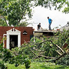 John P. Cleary | The Herald Bulletin <br /> Workers clear off the debris from what's left of the roof of this house on Fairlee Road near CR 600S.