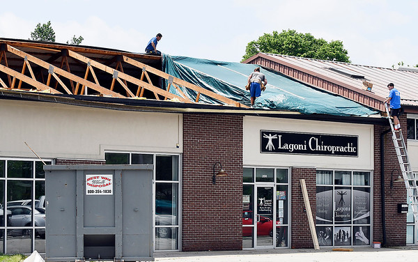 John P. Cleary | The Herald Bulletin <br /> Tornado cleanup starts in the Pendleton area after Monday's storms. Damaged roofs on businesses in the Huntsville area.