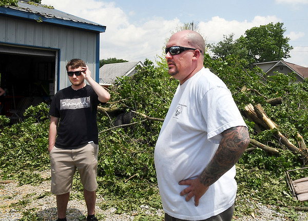 John P. Cleary | The Herald Bulletin <br /> Brian Hayden, right, got caught out in the storm Monday evening near her home on Market Street in Huntsville.