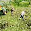 Don Knight | The Herald Bulletin<br /> From left, volunteers Coty Leffingwell and Chase Stanley stack branches into piles so the can be picked up by front loaders and carried off at Falls Park on Wednesday.