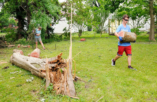 Don Knight | The Herald Bulletin<br /> Will Bluel moves a log as neighbors and volunteers came together in Pendleton to clean up after the town was hit by a tornado on Memorial Day.