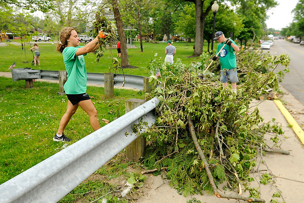 Don Knight   The Herald Bulletin<br /> Ally Hall moves brush to the sidewalk so it can be picked up at Falls Park on Wednesday. Hall was volunteering as part of the Pendleton Heights softball team. With school canceled several students turned out to help.