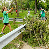 Don Knight | The Herald Bulletin<br /> Ally Hall moves brush to the sidewalk so it can be picked up at Falls Park on Wednesday. Hall was volunteering as part of the Pendleton Heights softball team. With school canceled several students turned out to help.