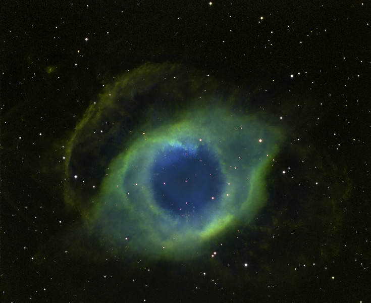 "Famous planetary nebula, the Helix in Aquarius. A pretty deep exposure (51 hrs) processed to bring out very faint outer features. H-alpha 31 hrs, OIII 20hrs. Mostly unbinned, some 2x2 binned, Mosaic of not-qute overlapping images from Aspen 16M and STL11000M. PlaneWave 20"" CDK.  Of great interest are the cometary knots seen as clumpy yellow-green streaks against the blue, radiating outward away from the blue-white central white dwarf. Notice the extremely faint chevron-like bow-wave shock fronts toward 9 o'clock., 10:30, and 11 o'clock. These structures average a flux of around just one photon per pixel per hour above background. There is a background galaxy clearly visible through the shocked material at 10:30, and several other tiny galaxies are visible in the image. North up. FOV approx half a degree."