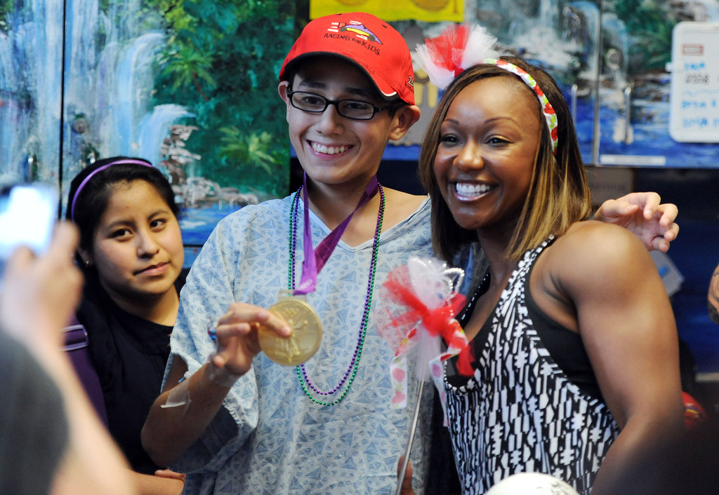 . Toyota Grand Prix of Long Beach Pro/Celebrity Race participant olympic sprinter Carmelita Jeter,left, poses for a photo with her 2012 gold medal, with Gabriel Odell-Perez,15, of Long Beach,  as she and other participants met some of the children at Miller Children�s Hospital at Long Beach Memorial Medical Center,  who will benefit from the proceeds generated by the 38th annual Toyota Grand Prix of Long Beach Pro/Celebrity Race.     Long Beach Calif., Thursday, April 10,  2014.   (Photo by Stephen Carr / Daily Breeze)